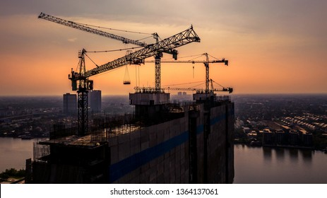 Construction site silhouette background, Hoisting cranes and new multi-storey buildings, Aerial view Industrial background.