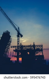 Construction site silhouette on sunset sky background vintage style