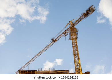 construction site with tower crane against the blue sky