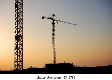 construction site with two cranes on sunset