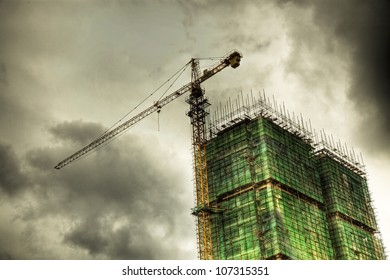 construction site under cloudy sky with green net and scaffold as protection.