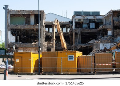 A construction site where a large building is being demolished, behind the fence are yellow containers