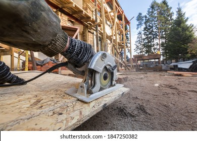 Construction Site. Construction worker with electrical circular saw saws the cement particle board oudoor near house that is under construction, remodeling, renovation, overhaul, extension