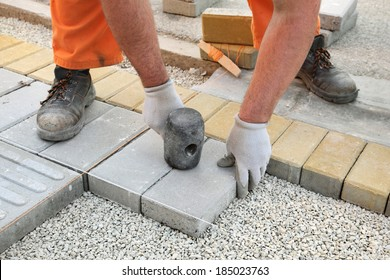 Construction site, worker installing concrete brick pavement, using hammer