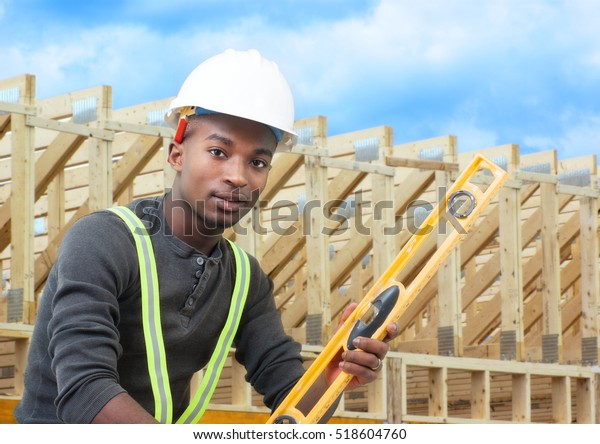 construction site worker with level helmet and beams background