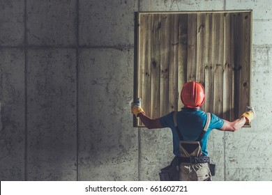 Construction Site Worker Lifting Wooden Element Up in the Air. Raw Concrete Interior.