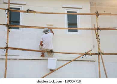 Construction site: worker on wooden scaffold painting house by roller