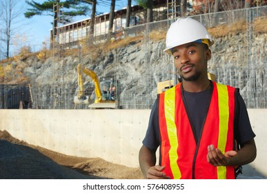 construction site worker orange jacket and white security helmet