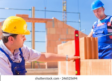 Construction site workers or bricklayer with helmets controlling building walls with a bubble level