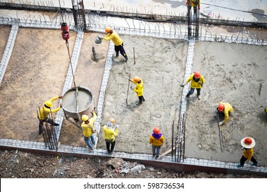 Construction site workers. Concrete pouring. Construction workers collaborating in the installation of cement formwork frames. workers leveling concrete pavement. Workers were plastering.