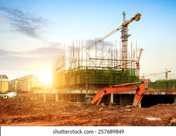 Construction site, workers and cranes.