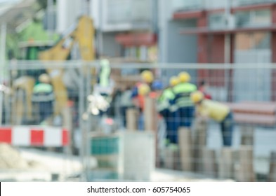 Construction site with workers and machinery on the street repair blurred image.