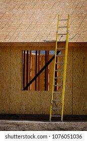 Construction site with yellow ladder with rough boards against wall
