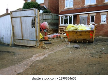 Construction site with yellow skip & building tools. Selective focus on full skip with space to add text in front of bin, wooden gate fence & brick houses in backgroud. Building renovation concept.
