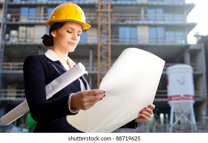 Construction specialist looking at blueprints at construction site