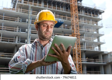 Construction specialist using a tablet computer. At a construction site.