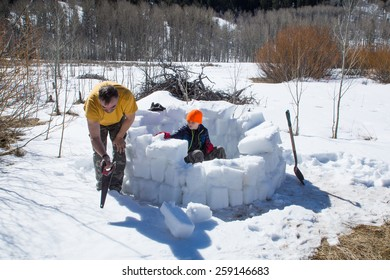 Construction Stages igloo - Eskimo dwelling. Adult cuts bricks of ice crust, the child strengthens the inside wall of snow built