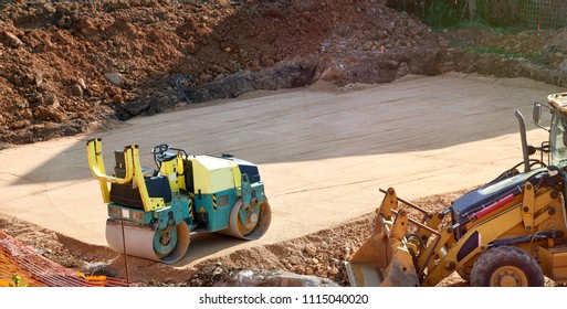 Construction steamroller and bulldozer on a house construction
