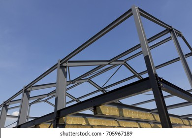 Construction steel work on a farm building in the English countryside with blue sky