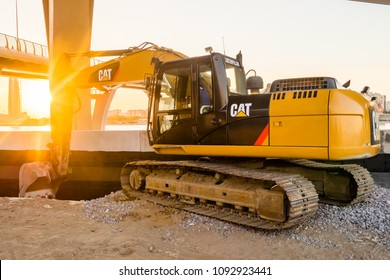 Construction of street of new emankment at St. Petersburg, Russia. Excavator CAT Caterpillar. Tractor with sunset shines. earthmoving, transportation. construction machinery concept.