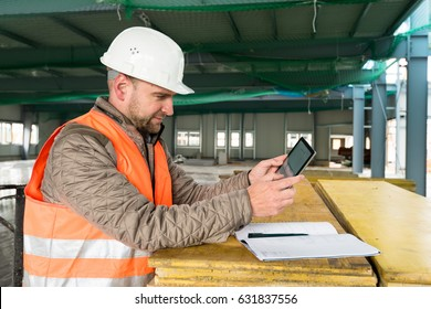Construction supervisor checks the interior of a new warehouse being constructed with a digital tablet in his hand and a plan lying besides him, wearing a safety helmet and vest