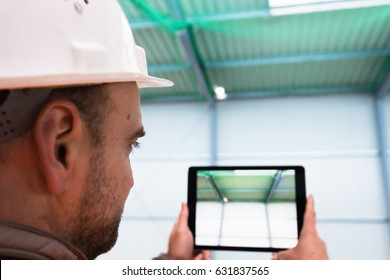 Construction supervisor checks the interior of a new warehouse being constructed while taking a photo with a digital tablet in his hand, wearing a safety helmet and vest