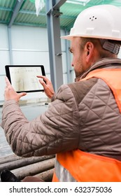 Construction supervisor checks the interior of a new warehouse being constructed with a digital tablet showing a map in his hand, wearing a safety helmet and vest. Focus on the digital tablets, the