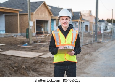 Construction supervisor standing in front of a home construction job site while holding a pencil.
