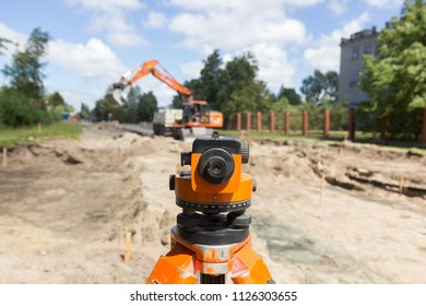 Construction surveyor equipment theodolite level tool with excavator at background