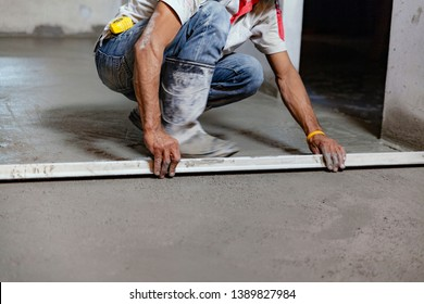 The construction technician is working by leveling the concrete floor to be smooth.