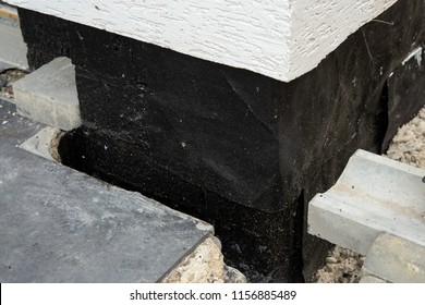 Construction techniques for waterproofing basement and foundations. Insulation material on the basement concrete wall. Waterproofing house foundation with spray on tar and roll waterproofing