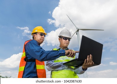 Construction or Technology Project Development Concept, Male Architect and Engineer use Laptop computer white working in Wind Power Farm under Wind Turbine Power Generator Tower