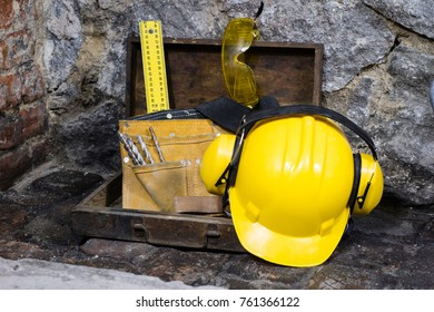 Construction tools for building a house on a stone wall. Hammer, helmet, and other necessary tools for construction or splitting. House construction area.