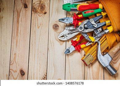 construction tools in leather toolbelt on wooden boards