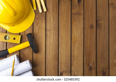 Construction tools on a wooden background