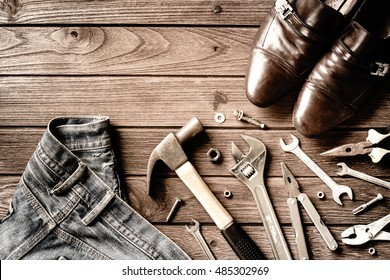 Construction tools, shoes and jeans on wooden background