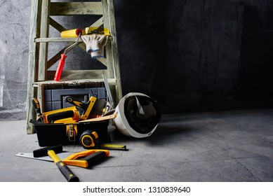Construction tools and stepladder on a black wall background. Repairs
