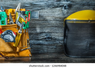 construction tools in toolbelt and safety mask on vintage wood