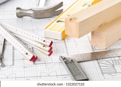 Construction tools and wooden strips on architectural blueprint house building plan on table