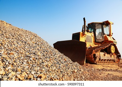 it is construction tractor working with pile of gravel and sky.