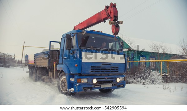 Construction truck in snow-covered winter village at sunny day, wide angle