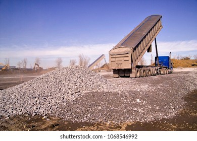 Construction truck tipping dumping gravel on road construction site