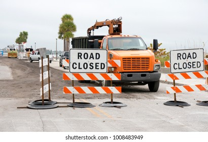 Construction trucks working on a road behind road closed signs.