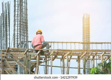 Construction of unfinished building with man work on site.