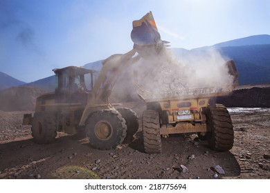 Construction vehicles on building site with dust filled air and blue mountains background