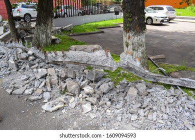 Construction waste near trees and a car parking space. Rubbish in the city near a park area with trees and lawns. Broken concrete slabs after government issued order to remove all fences in the city.