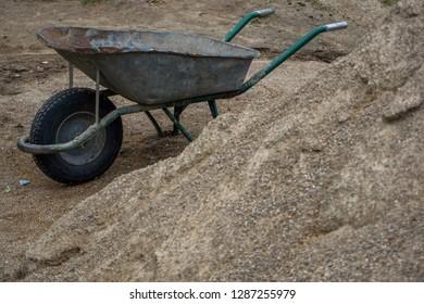 Construction wheelbarrow in the sand by the river Daugava. Wheelbarrow at the gravel pile, Latvia. Wheelbarrow for construction in site building area.