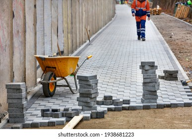 Construction wheelbarrow and stacks of paving slabs against blurred background of lined walkway and walking worker in orange overalls. Copy space.
