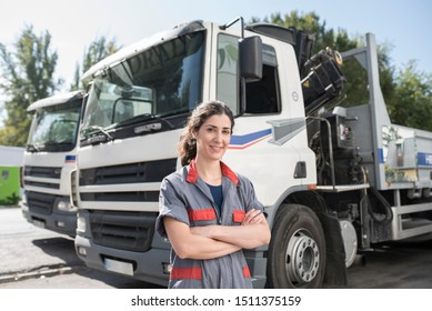Construction woman worker near to iron structures transportation trucks smiling