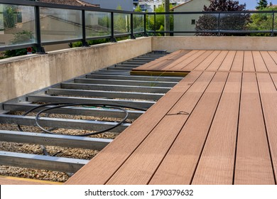Construction of a wooden terrace on a balcony. A new wooden, timber deck being constructed. City background.